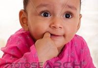 Awesome beautiful african american ba girl with his finger in the mout stock image Beautiful African American Children